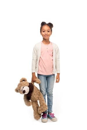 adorable african american child holding teddy bear and smiling at camera isolated on white