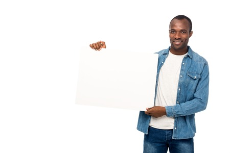 handsome african american man holding blank banner and smiling at camera isolated on white