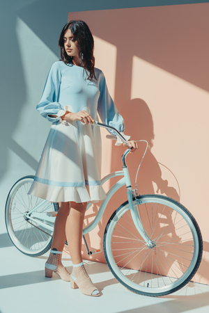 Beautiful woman standing in fashionable turquoise dress with long sleeves holding bicycle and looking down
