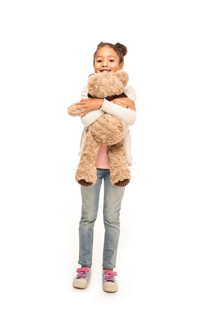 cute african american child hugging teddy bear and smiling at camera isolated on white Stock Photo