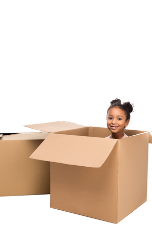 cute african american kid sitting in cardboard box and smiling at camera isolated on white