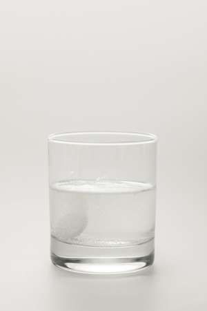 effervescent pill in glass of water isolated on white Фото со стока