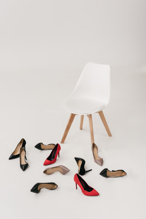empty modern chair and stylish high heeled shoes isolated on grey Stock Photo
