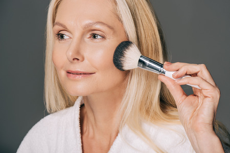 close-up portrait of mature woman doing makeup isolated on grey 写真素材