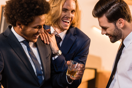 three multiethnic businessmen laughing while drinking whiskey in bar
