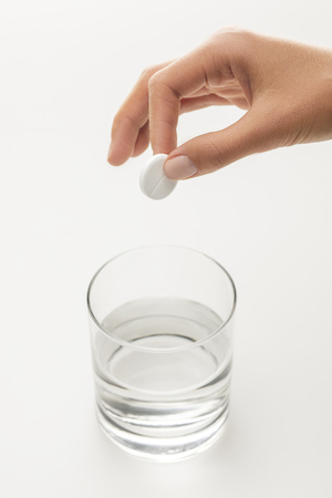 cropped image of woman putting effervescent pill into glass of water isolated on white Banco de Imagens