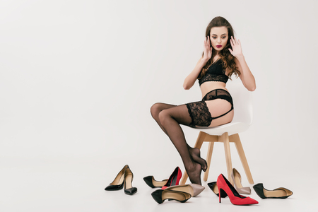 surprised young woman in lingerie sitting on chair and looking at various high heeled shoes isolated on grey