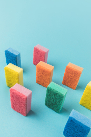 studio shot of colorful washing kitchen sponges, on blue with copy space Stock Photo