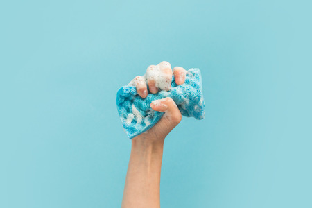 cropped view of hand holding washing sponge with foam, isolated on blue