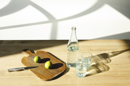 mineral water and limes for preparing lemonade on wooden table
