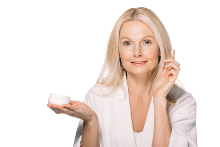 attractive mature woman applying cosmetic cream isolated on white Reklamní fotografie