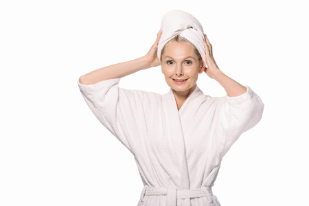 beautiful middle aged woman in bath robe and towel on head isolated on white