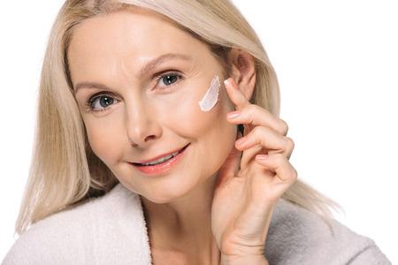 Femme mature souriante, appliquer la crème cosmétique isolée sur blanc