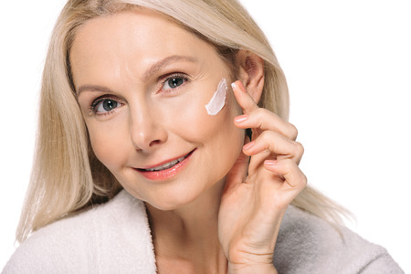 smiling mature woman applying cosmetic cream isolated on white