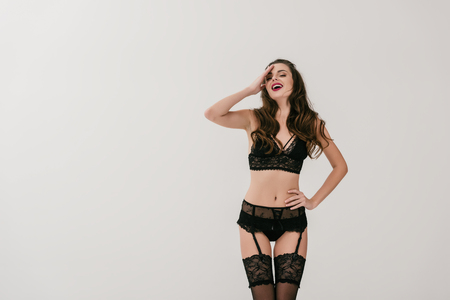 sensual young woman in black lingerie and stockings laughing and posing isolated on grey Stock Photo