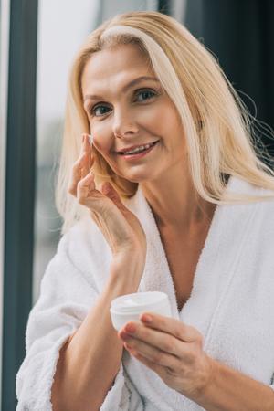 happy mature woman in bath robe applying cosmetic cream