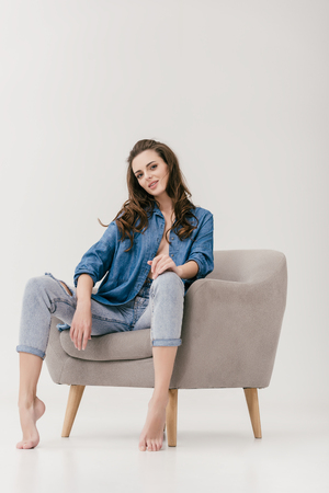 seductive young woman in denim clothes sitting on chair and looking at camera isolated on grey Reklamní fotografie