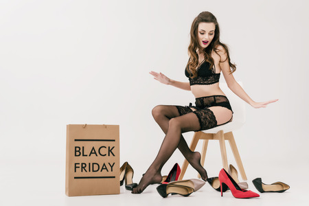beautiful surprised girl in underwear looking at fashionable shoes while sitting with shopping bag isolated on grey Standard-Bild