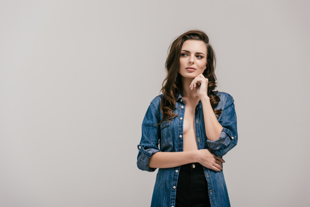thoughtful young woman in denim shirt standing with hand on chin and looking away isolated on grey