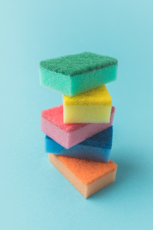 pile of colorful washing kitchen sponges, isolated on blue