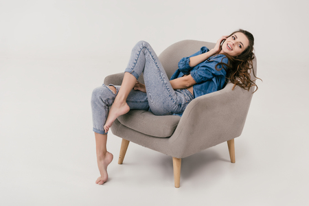 beautiful smiling sexy woman in denim clothes sitting on armchair and looking away isolated on grey Zdjęcie Seryjne - 102660417