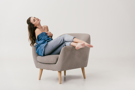 seductive young woman with naked shoulders sitting with closed eyes on armchair isolated on grey Stock fotó