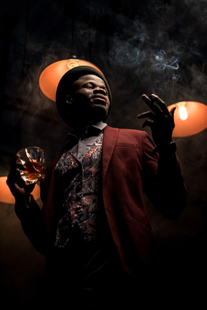 handsome elegant african american man in hat smoking cigar and drinking whiskey in dark room with lamps Zdjęcie Seryjne