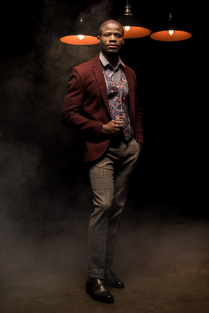 handsome fashionable african american man holding glass of cognac in dark smoky room with lamps Stock Photo