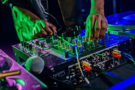 cropped view of DJ in with sound mixer and microphone in nightclub  Stock Photo