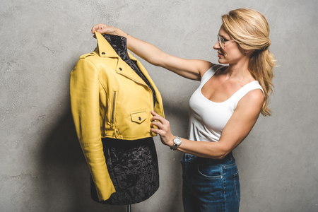 attractive mature dressmaker with yellow leather jacket on mannequin Stockfoto