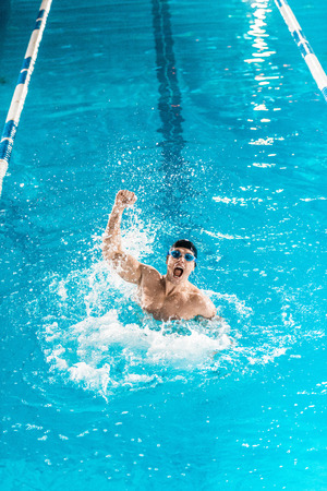 excited swimmer gesturing and making splash in competition swimming pool