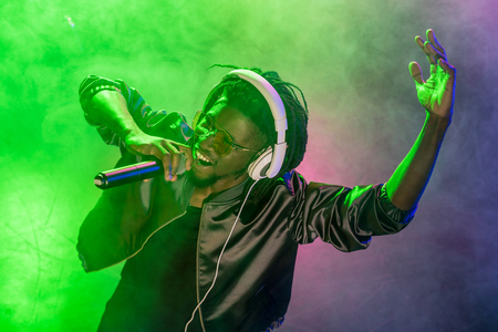professional african american club DJ in headphones singing with microphone on music concert