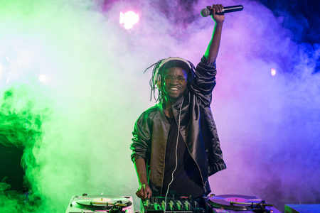 professional african american club DJ in headphones with sound mixer and microphone in nightclub