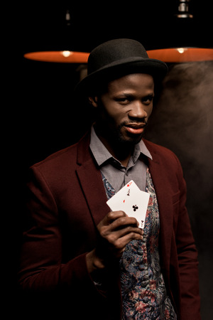 handsome elegant african american man with playing cards in hands in dark room with lamps Stock Photo