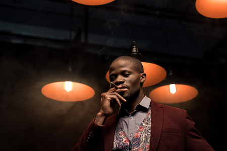 handsome african american man smoking cigar in dark room with lamps Stock Photo