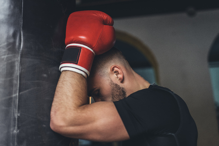 side view of muscular young boxer leaning at punching bag