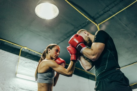 low angle view of young male and female boxers training on boxing ring