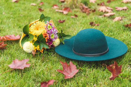 felt hat and bouquet of flowers on green lawn with foliage