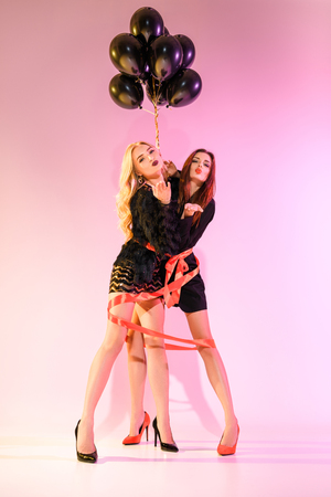 young glamorous girls bound with red ribbon and black balloons on pink