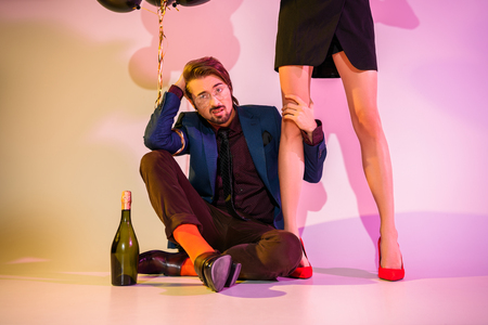 stylish couple posing with champagne bottle and black balloons on pink