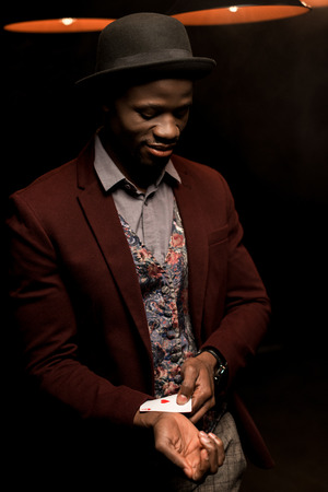 handsome elegant african american man with ace in sleeve in dark room with lamps Stock Photo