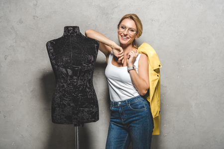 beautiful smiling mature seamstress with yellow leather jacket and mannequin Stockfoto