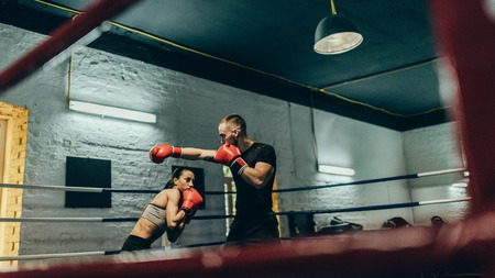 athletic young couple of boxers training on boxing ring Stock Photo