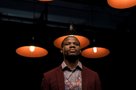 stylish elegant african american man in jacket with lamps
