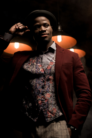 handsome african american man in hat posing in dark room with lamps