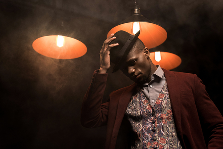 handsome stylish african american man in hat posing in dark room with lamps Stock Photo