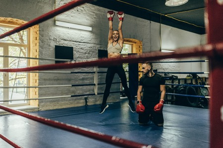 young female boxer triumphing while male boxer kneeling on boxing ring