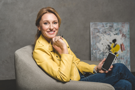 smiling mature woman using smartphone and sitting in armchair