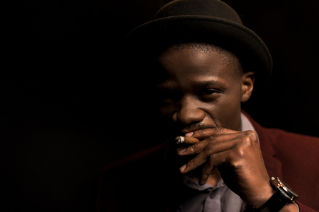 portrait of handsome african american man in hat smoking cigar,  isolated on black Stock Photo - 102660923