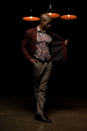 luxury handsome african american man posing in dark room with lamps